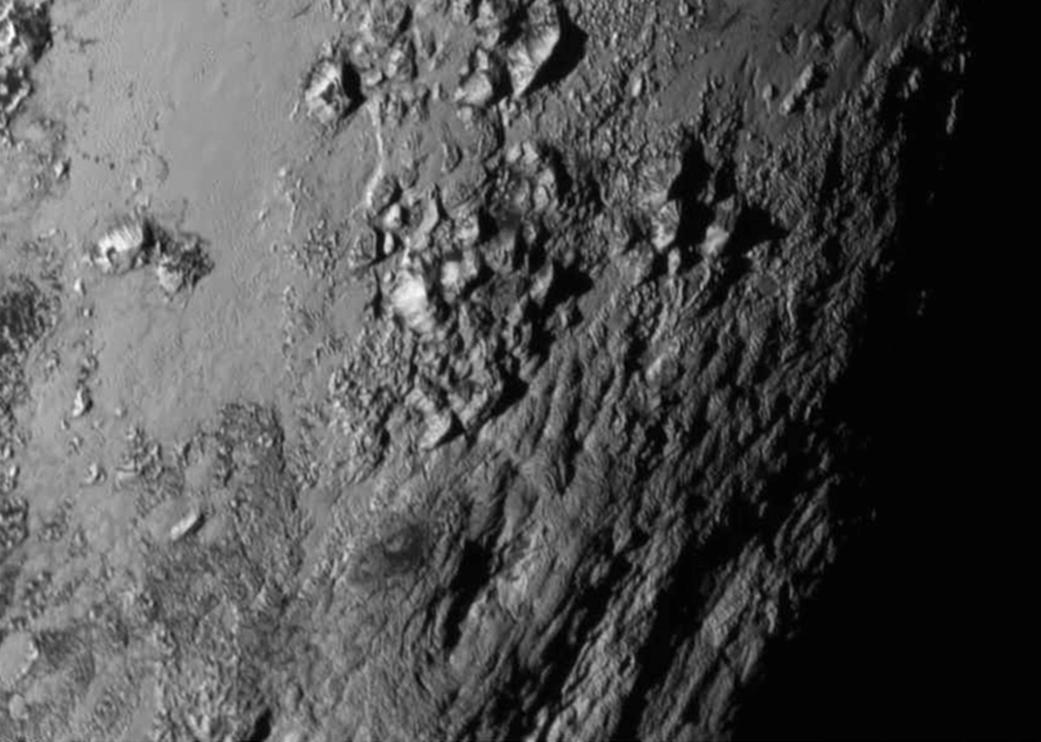 Voici un petit bout de la surface de Pluton. Les rugosités seraient en fait des montagnes de glace d'eau. Il y aurait donc de l'eau sur Pluton