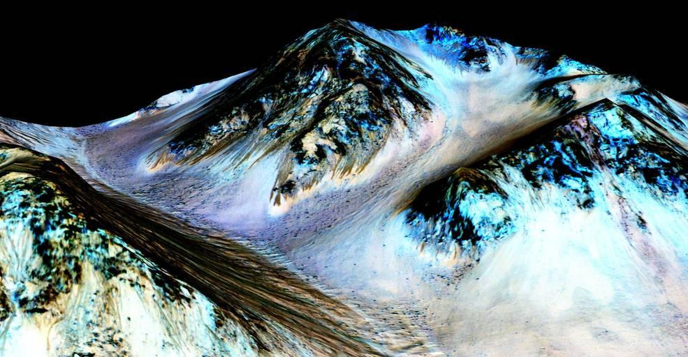 Cette photo a été prise par le spectrographe du MRO. Elle représente un paysage montagneux dont les couleurs ont volontairement été changées afin de faire ressortir la présence des minéraux hydratés ici visibles en bleu. [Credits: NASA/JPL/University of Arizona]