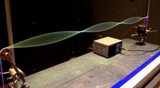 Voici une photo d'un dispositif expérimental permettant de faire vibrer une corde à une fréquence bien précise. On reconnait bien les ondes transversales ici.